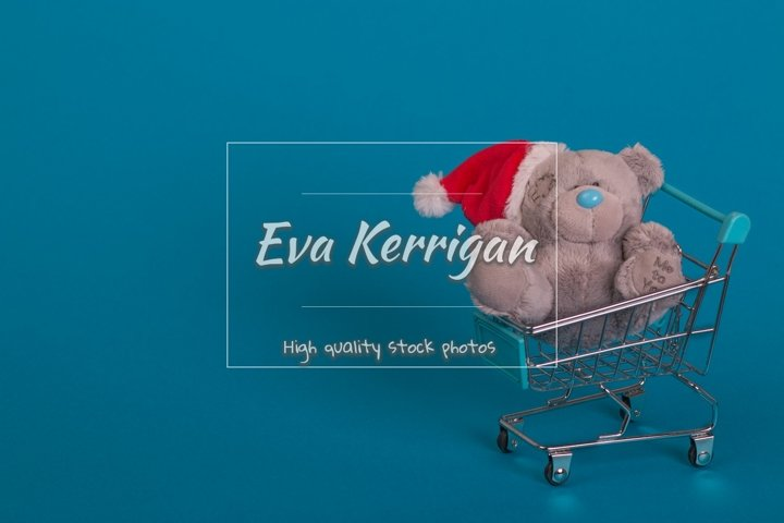 A supermarket trolley on a blue background and bear toy.
