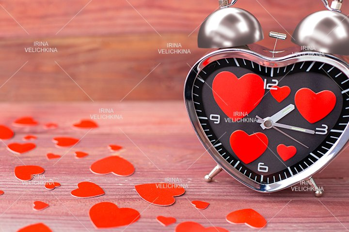 Steel alarm clock. Red hearts on wooden background.Valentine