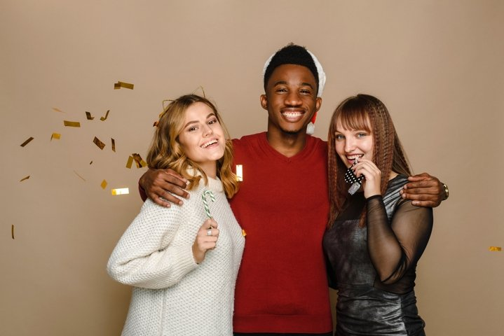 Three multi-ethnic friends celebrate Christmas and New Year