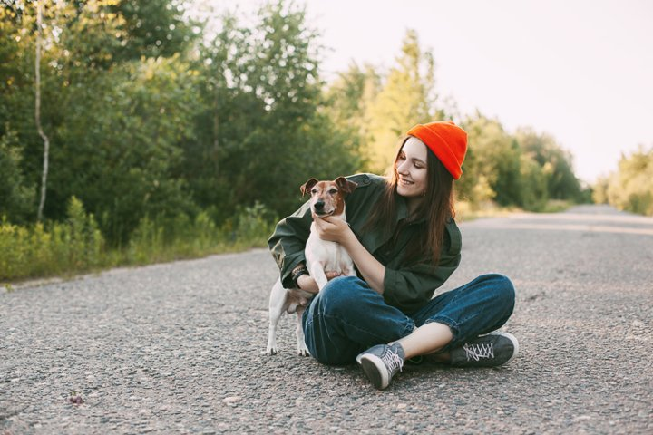 A charming teenage girl in an orange hat sits with her dog