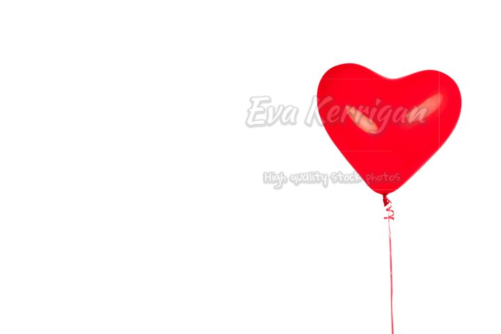 Red bright air rubber balloon in shape of heart isolated.