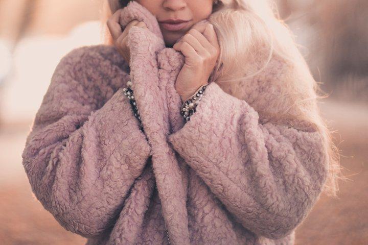 Stylish woman holding coat