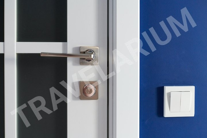 White interior door with handle. Blue wall