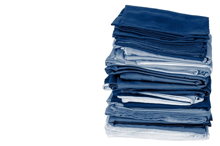 Stack of folded clean blue bedding on white background