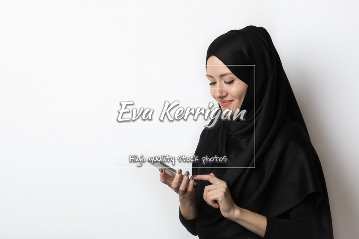 A beautiful Muslim woman is looking on the phone.