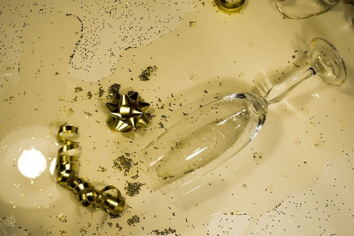 Festive still life with spilled champagne, sparkles