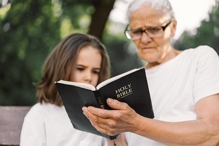 Grandmother and little girl reading holy bible