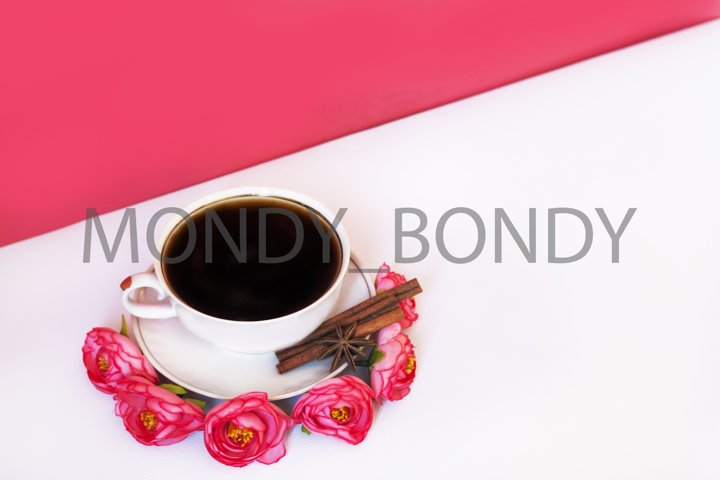 Cup of coffee with cinnamon on a pink background