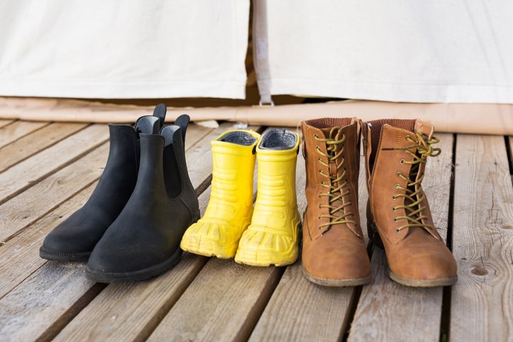 Close-up of three pair of shoes on wooden terrace in camping