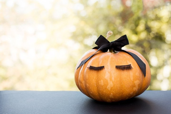 Halloween pumpkin with make up eyelashes and black bow