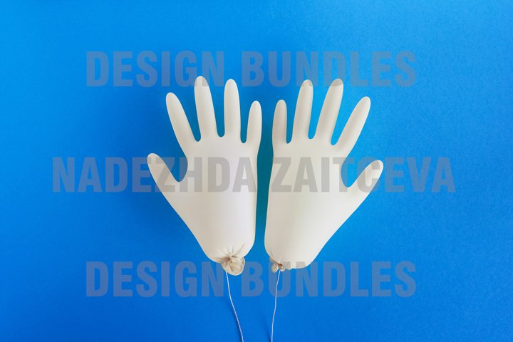 Pair of disposable medical gloves on blue background.