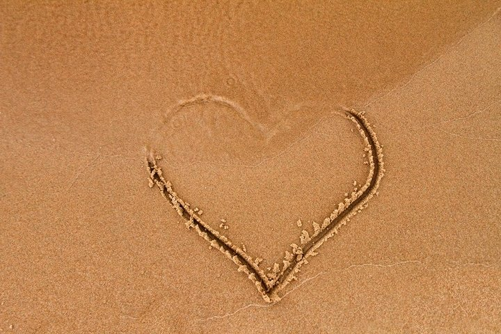 Hand-drawn heart shape on wet yellow sand, covered by wave