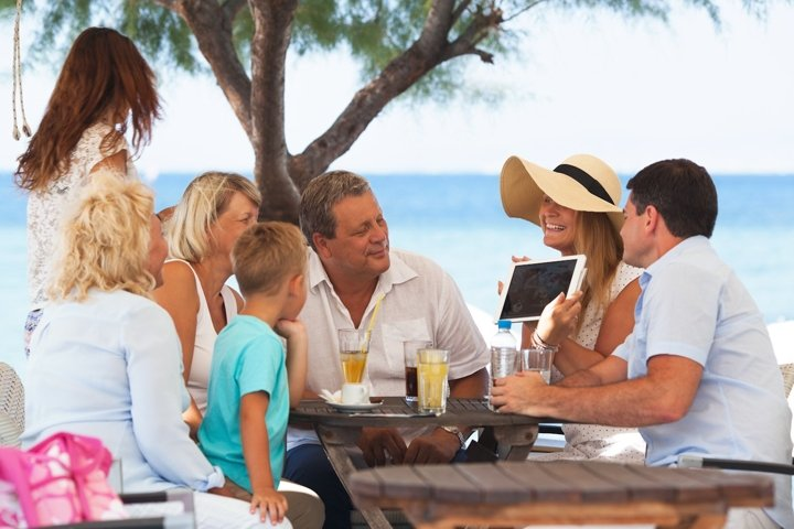 Family looking at photo on touch pad in outdoor cafe