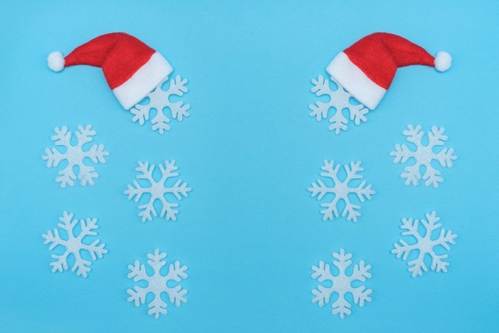 Santa Claus hats and snowflakes on pastel blue background.