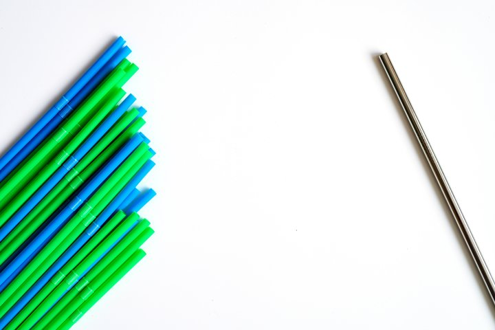 pile of plastic straws and one reusable metal drinking straw