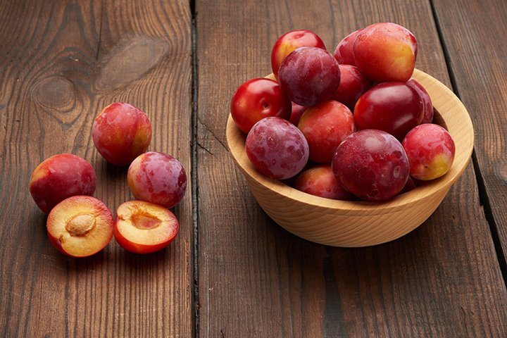 ripe red plums in a round wooden plate