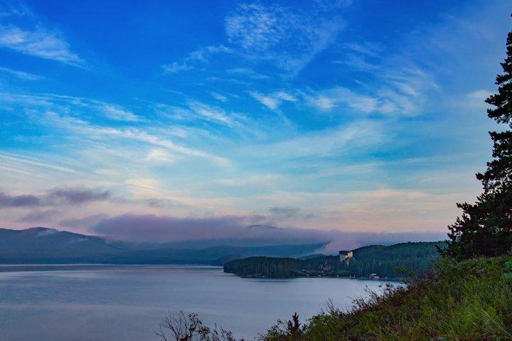 Foggy sunrise over the mountain lake Turgoyak.