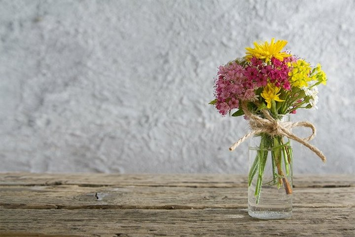 Miniature glass bottle with wildflowers copy space