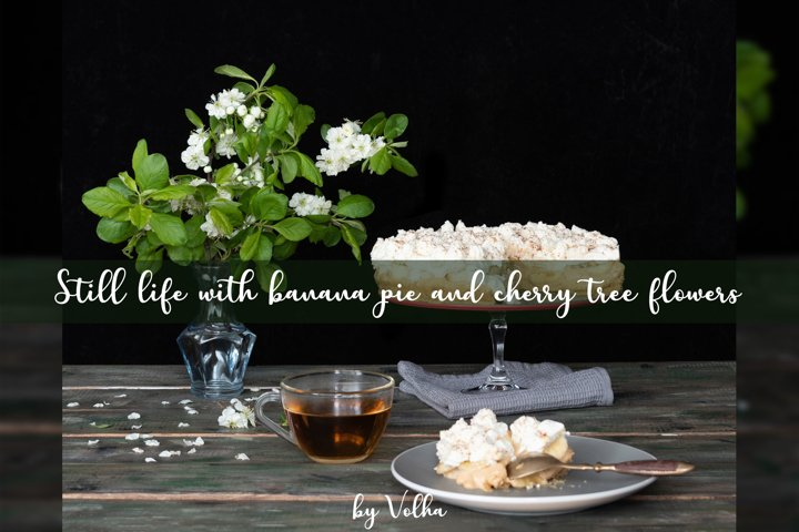 Still life with banana pie and cherry tree flowers