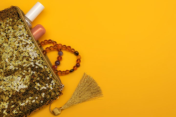Gold womens cosmetic bag on a yellow background