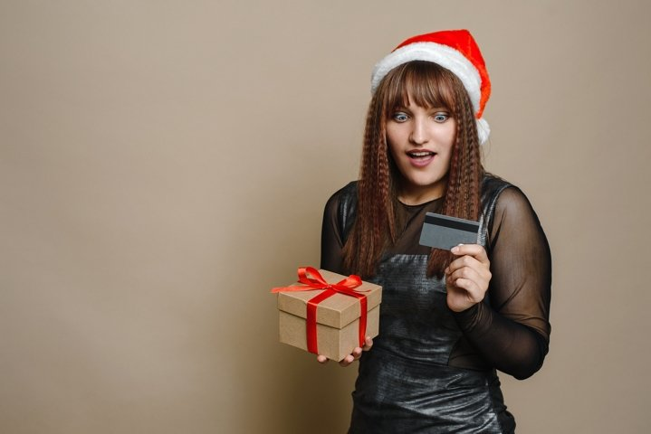 Surprised young woman in santa claus hat