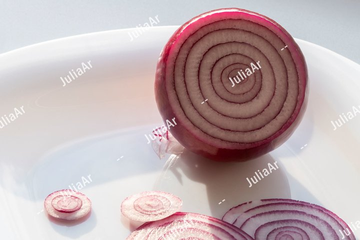 Red onion and slices on white plate