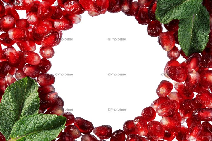 Pomegranate or garnet red seeds frame with mint leaves