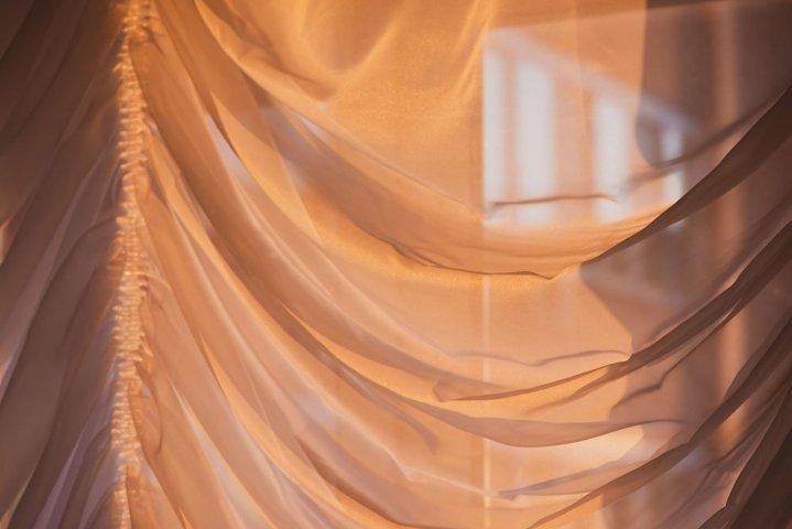 Elegant, thin transparent curtain on window, by sunshine