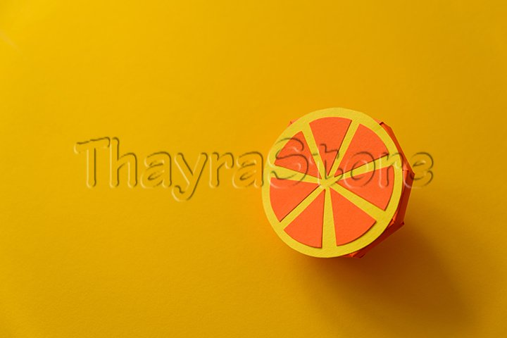 Paper orange fruit on yellow background.
