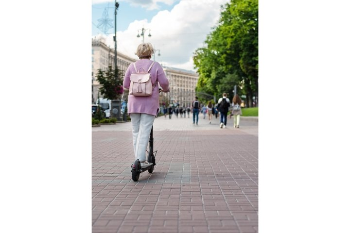 Active adult woman riding electric push scooter in the city
