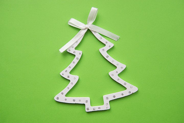 Decorative wooden white Christmas tree on a green background