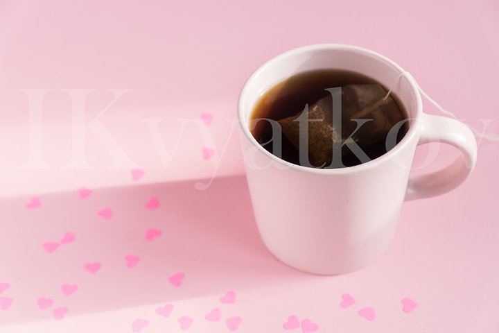 Pink cup with hot black tea on pink background