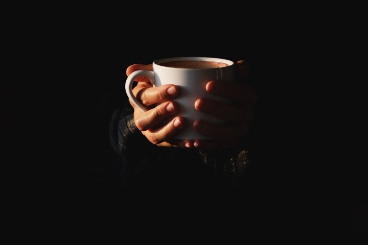 Female hands holding white cup of coffee on black background