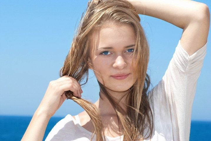 Beautiful blond girl with long hair with blue sea