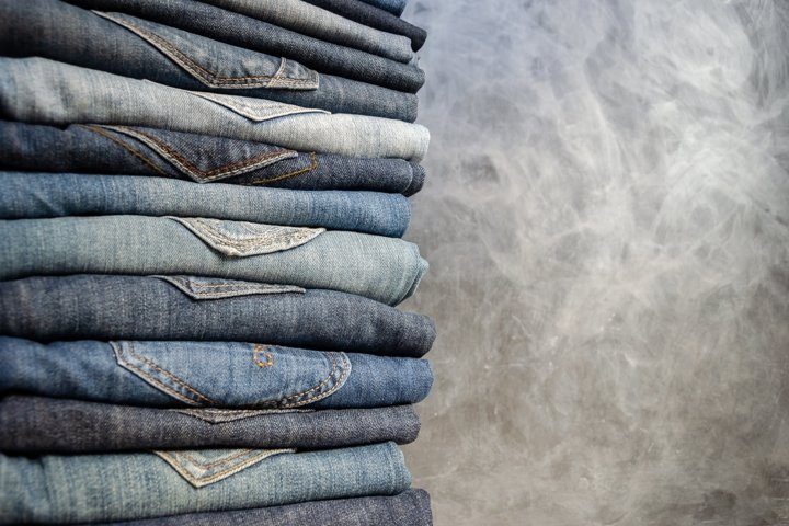 Stack of neatly folded womans jeans on gray background