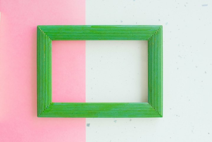 Wooden green photo frame on white and pink background
