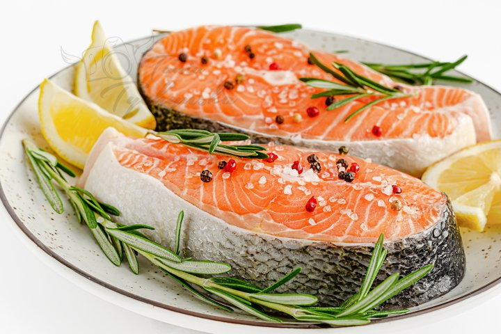 Raw salmon fish steaks with pepper, salt, rosemary and lemon