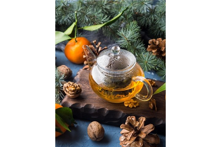 Winter tea in pot and tangerines with pine cones