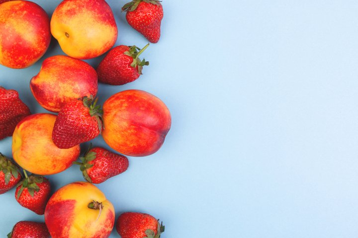 Peaches and strawberries on a blue background.