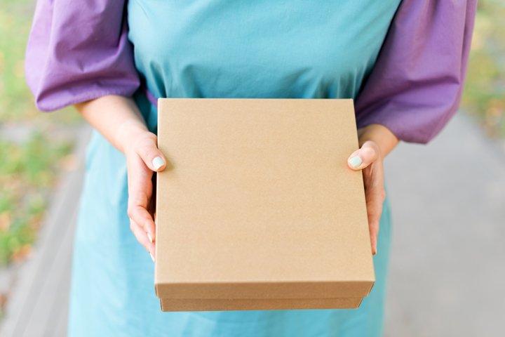 Female hands holding cardboard gift box