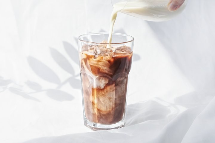 Milk cream is poured into a iced coffee.