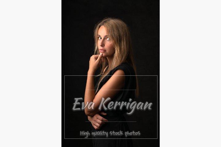A beautiful pensive blonde girl stands in half a turn.