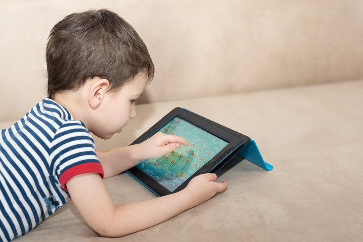 Toddler boy lie on the sofa with a tablet studying English.