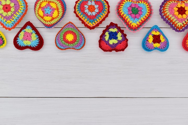 Knitted hearts are placed on white wooden boards.