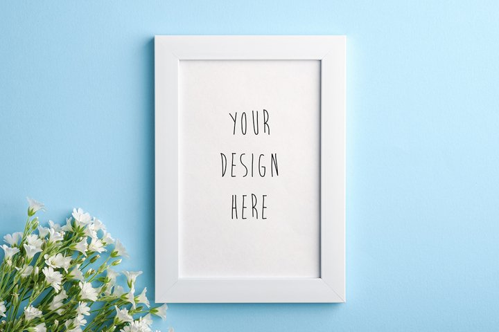 Photo frame mockup with flowers on blue background