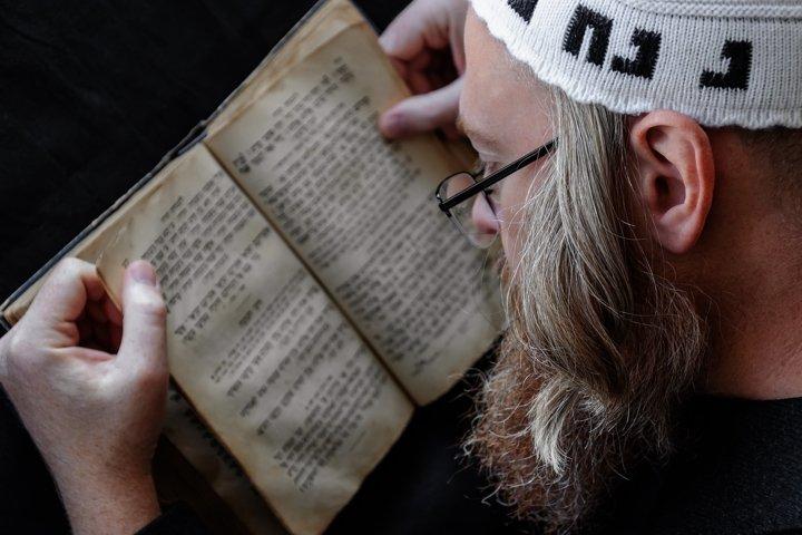 Hasidic Jew reading Siddur. Praying religious orthodox Jew