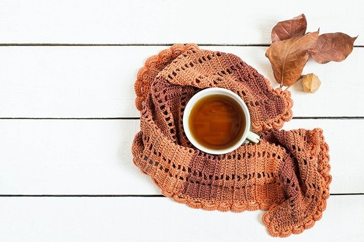Cup of tea, knitted scarf and dry autumn leaves