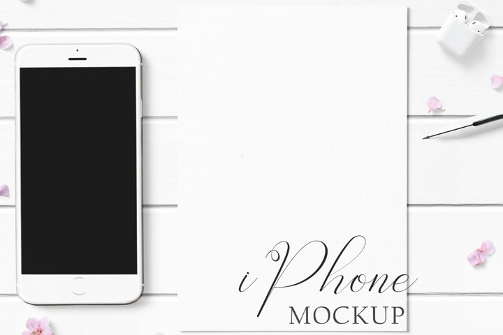 iPhone Mockup with pink flowers on a white wood background.