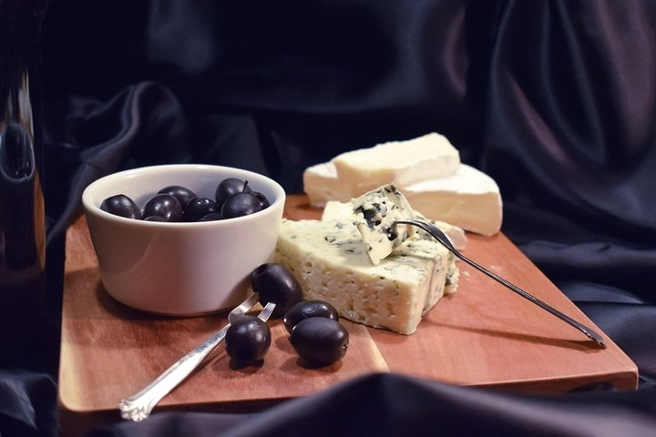 Olives, French cheese on a black background
