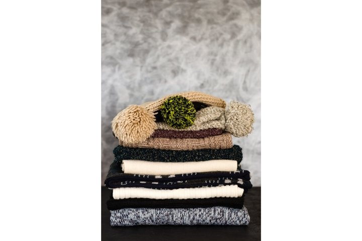 Stack of folded knitted winter scarves and hats on gray